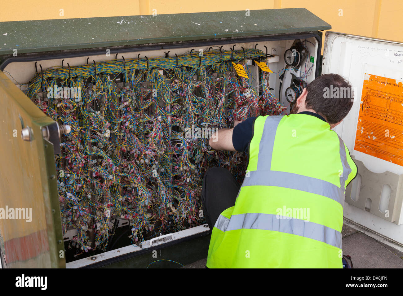 Engineer working on BT street telephone wiring box. - Stock Image