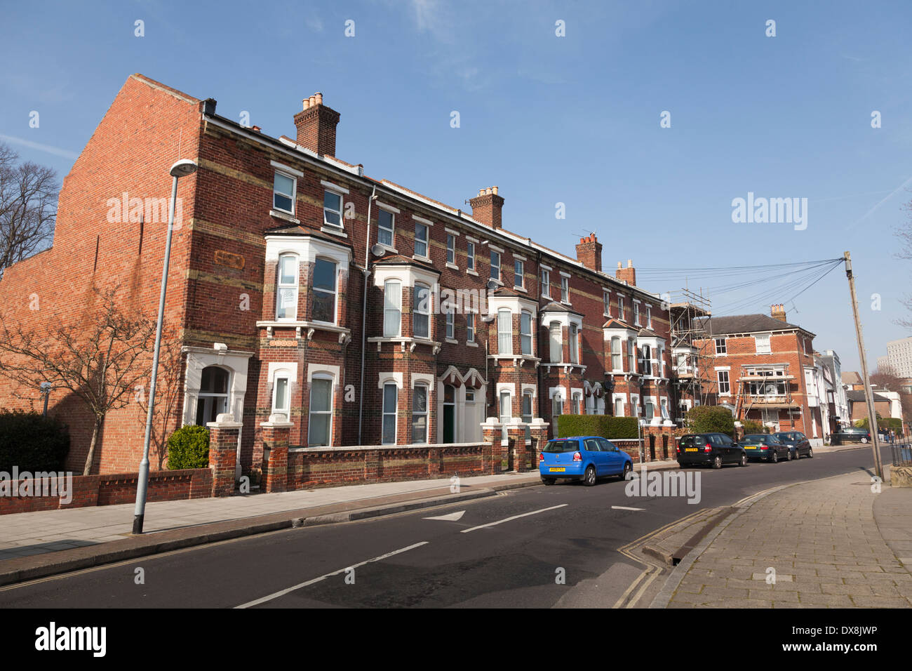Three storey terrace houses with bay windows and front gardens. - Stock Image