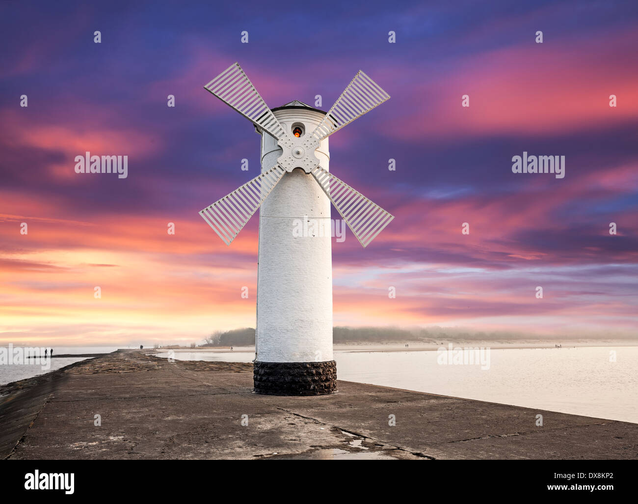 Lighthouse windmill with dramatic sunset sky, Swinoujscie, Baltic Sea, Poland. Stock Photo