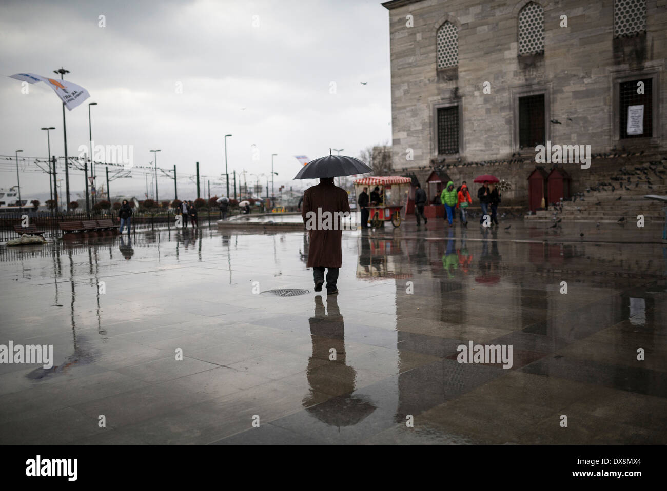 A man protect himself with umbrella as walks past the New Mosque in Eminonu district in Istanbul, Turkey on March 2014. - Stock Image