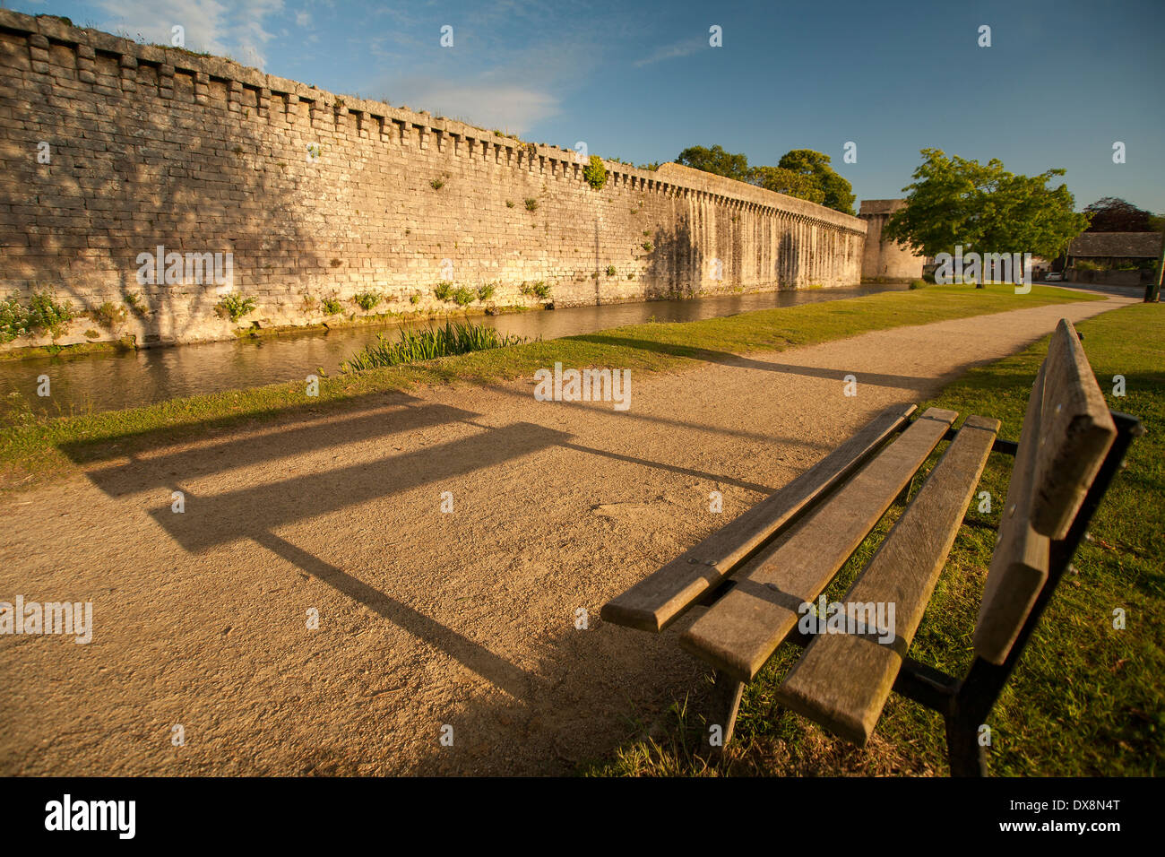 Public bench facing path castle wall and moat. Stock Photo