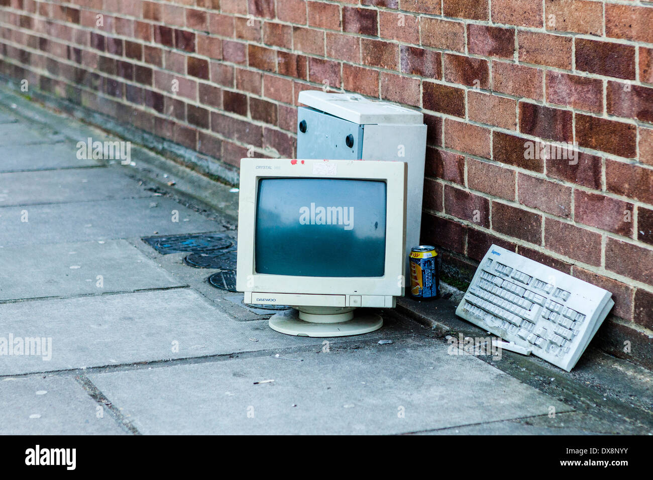Old broken redundant Daewoo computer, screen and keyboard dumped on a pavement in London, UK - Stock Image
