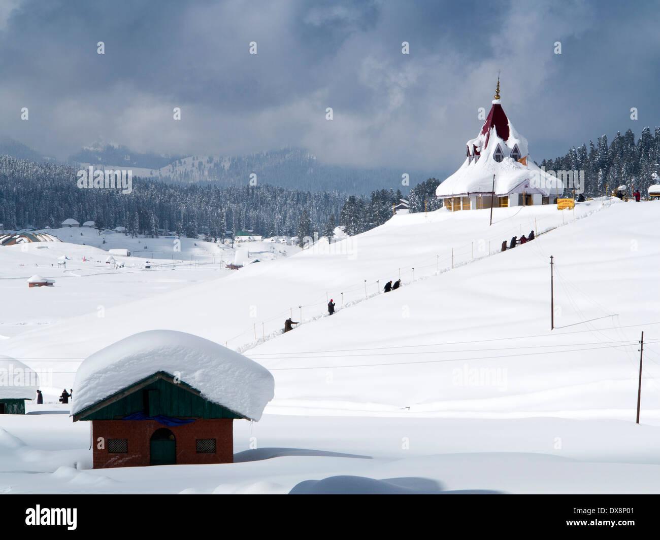 india, kashmir, gulmarg, himalayan ski resort, men walking to snow