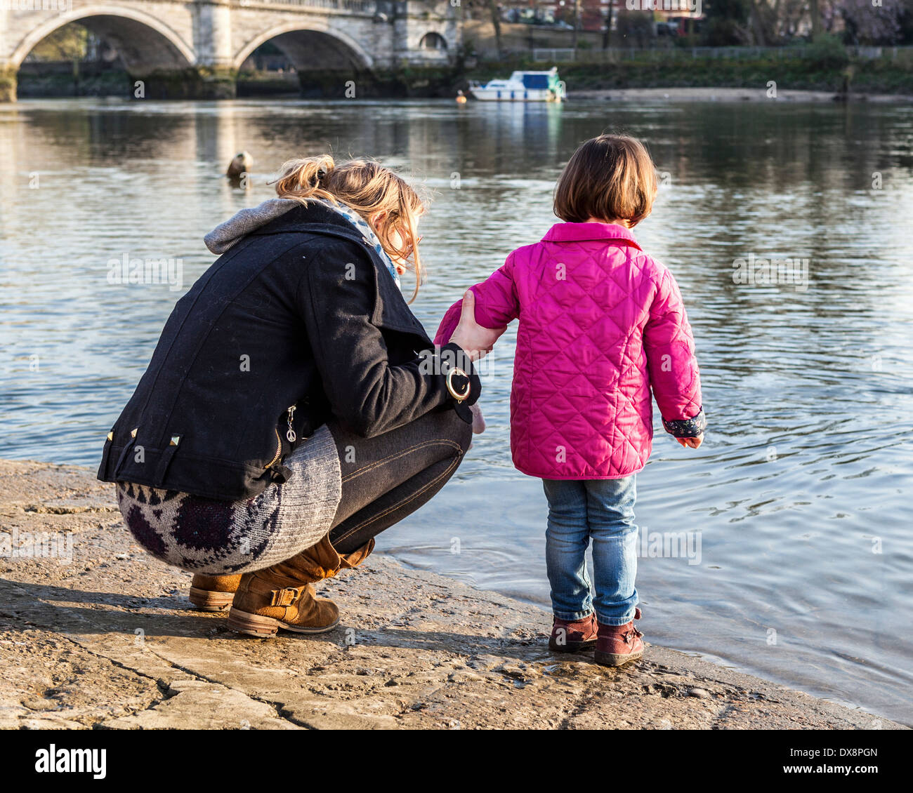 Woman holds arm of young child in pink coat on banks of river Thames, Richmond upon Thames, London, UK - Stock Image