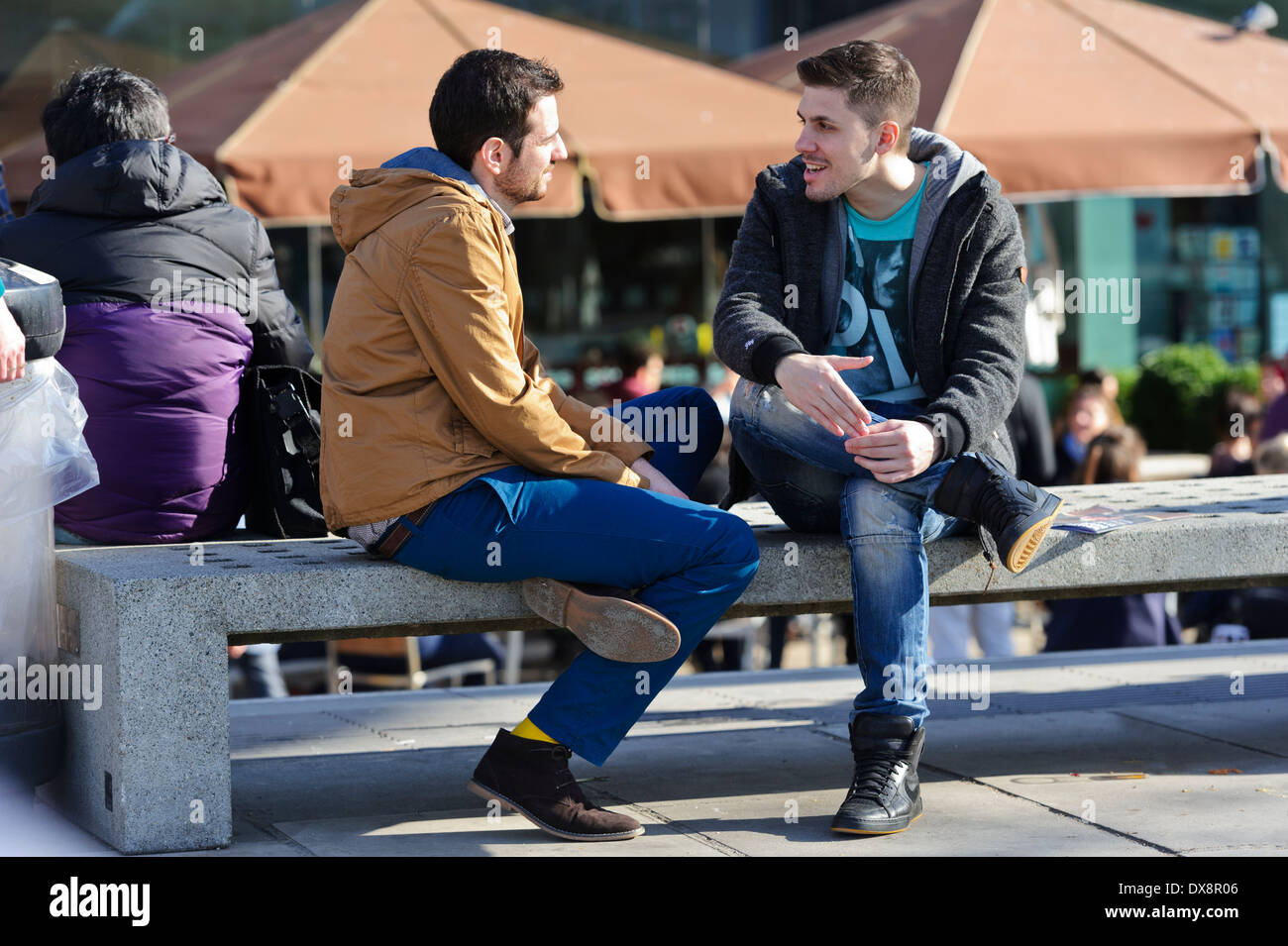 Two young men sitting on a concert bench dressed in winter