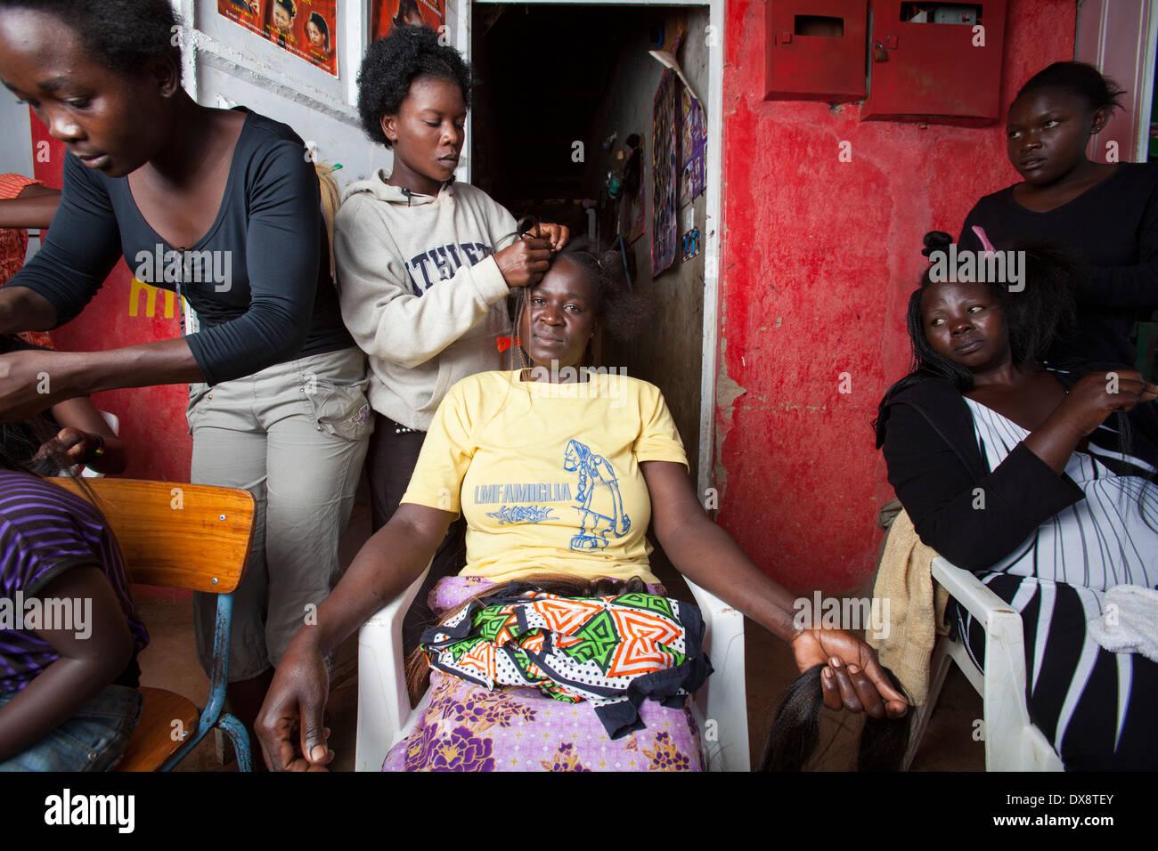 Woman having hair braided at a hair salon, Kisumu region, Kenya - Stock Image