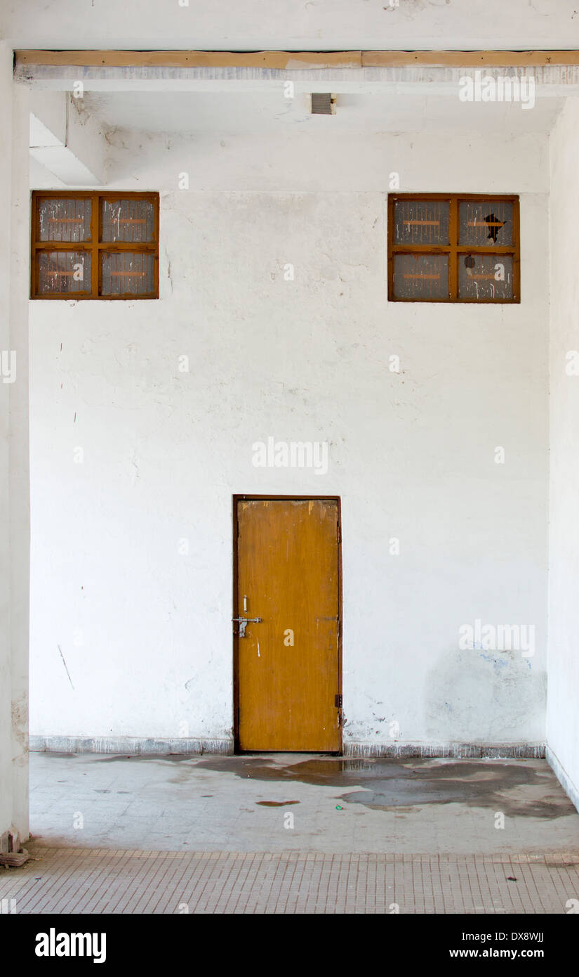 A door and two windows in a whitewashed wall - Stock Image