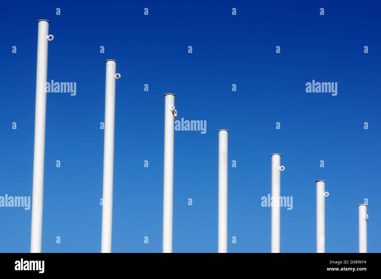 empty white flag poles against blue sky - Stock Image