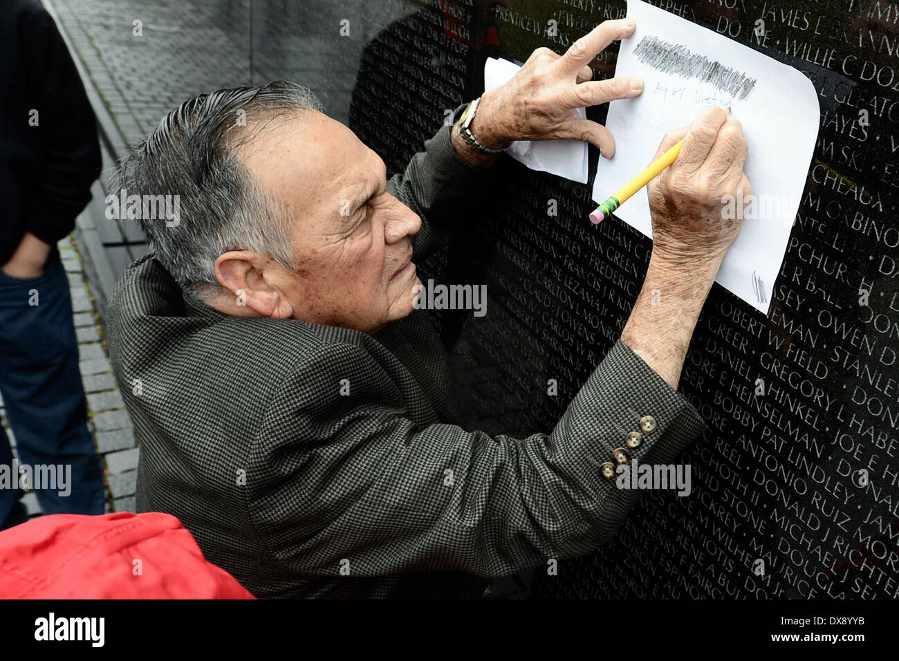 Washington DC, USA . 19th Mar, 2014. Medal of Honor recipient Army Master Sgt. Jose Rodela stencils a friend's name from the Vietnam Veterans Memorial March 19, 2014 in Washington, D.C. Credit:  Planetpix/Alamy Live News - Stock Image