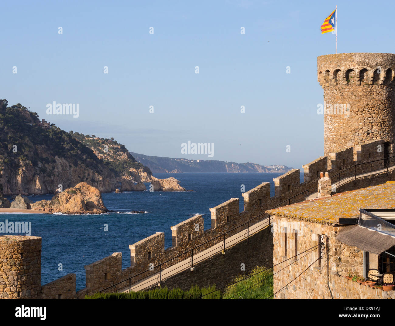 Tossa de Mar Castle overlooking the sea. A fortified hill topped by a Catalonian flag looks over the blue Mediterranean Sea. - Stock Image