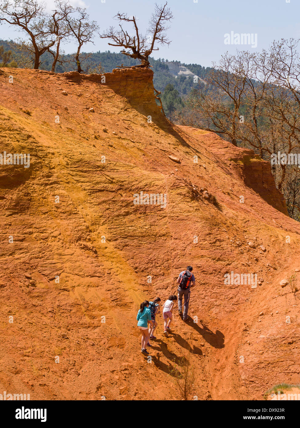 Family Climbing. A father and three girls climb up the red face of the rock at Le Colorado Provençal de Rustrel. - Stock Image