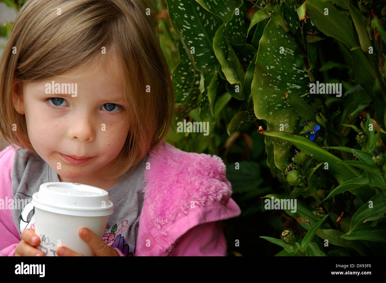 Little girl cools down her hot chocolate.Stock Photo