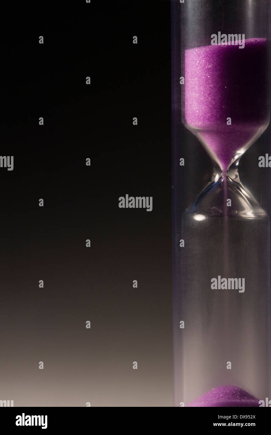 Hourglass with most of the sand in the top - Stock Image