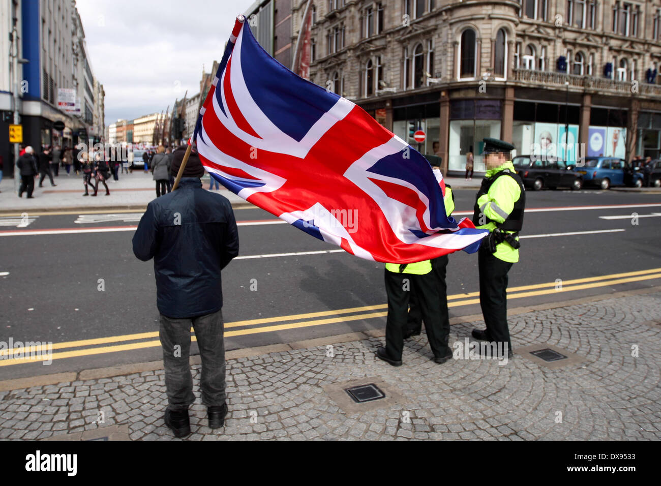 Belfast UK, 8th March 2014.  Loyalist Flag protester waves union flag outside Belfast City Hall with Police onlookers - Stock Image