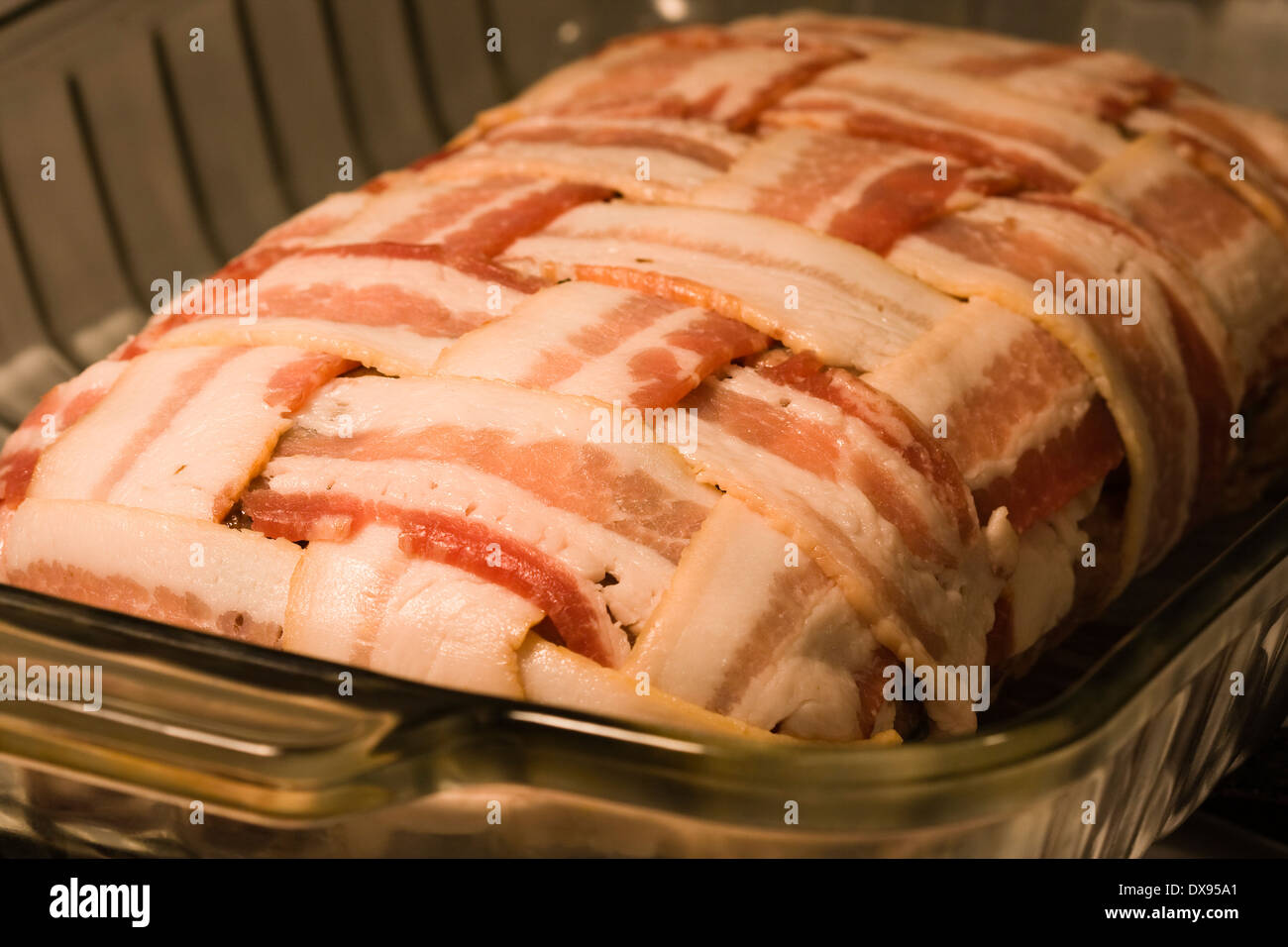 Uncooked Meatloaf wrapped with bacon in a basket weave pattern sitting in a clear Pyrex baking dish on a kitchen stovetop - Stock Image