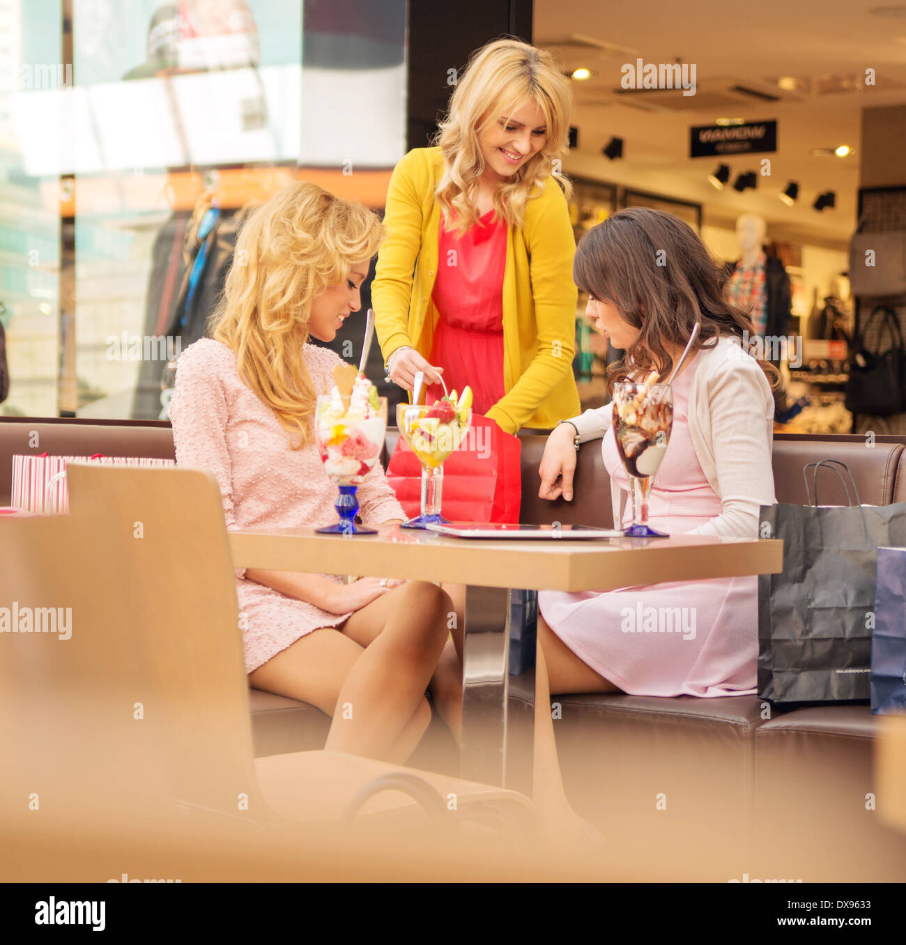Three young cheerful girlfriends at the short break - Stock Image