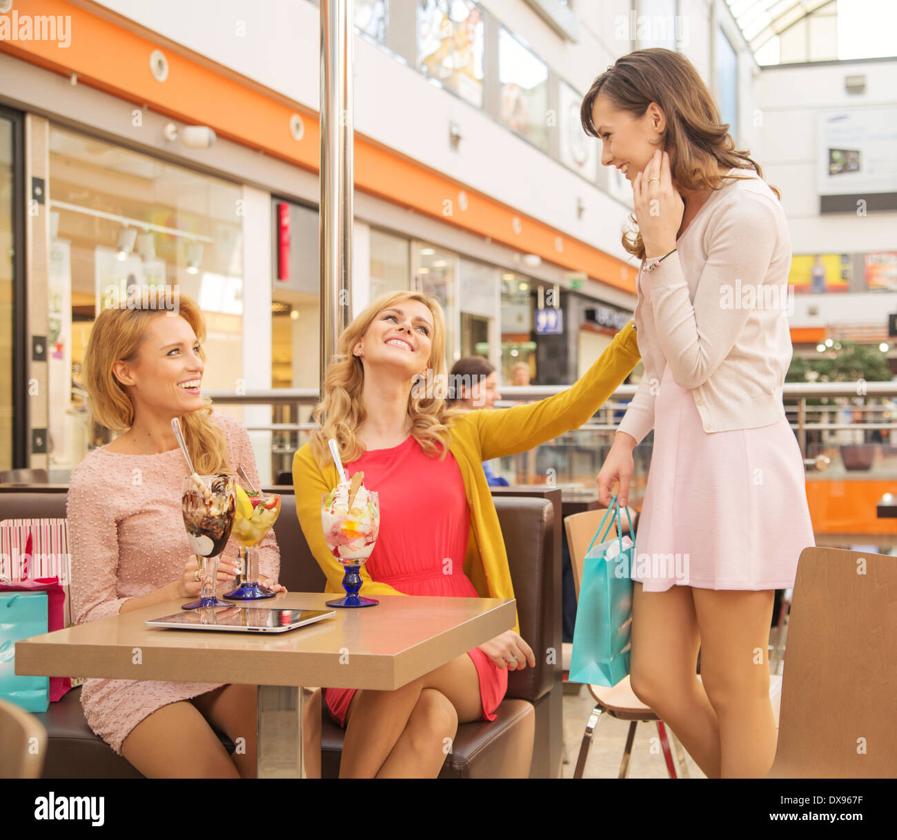 Laughing female friends in the small shopping mall cafee - Stock Image