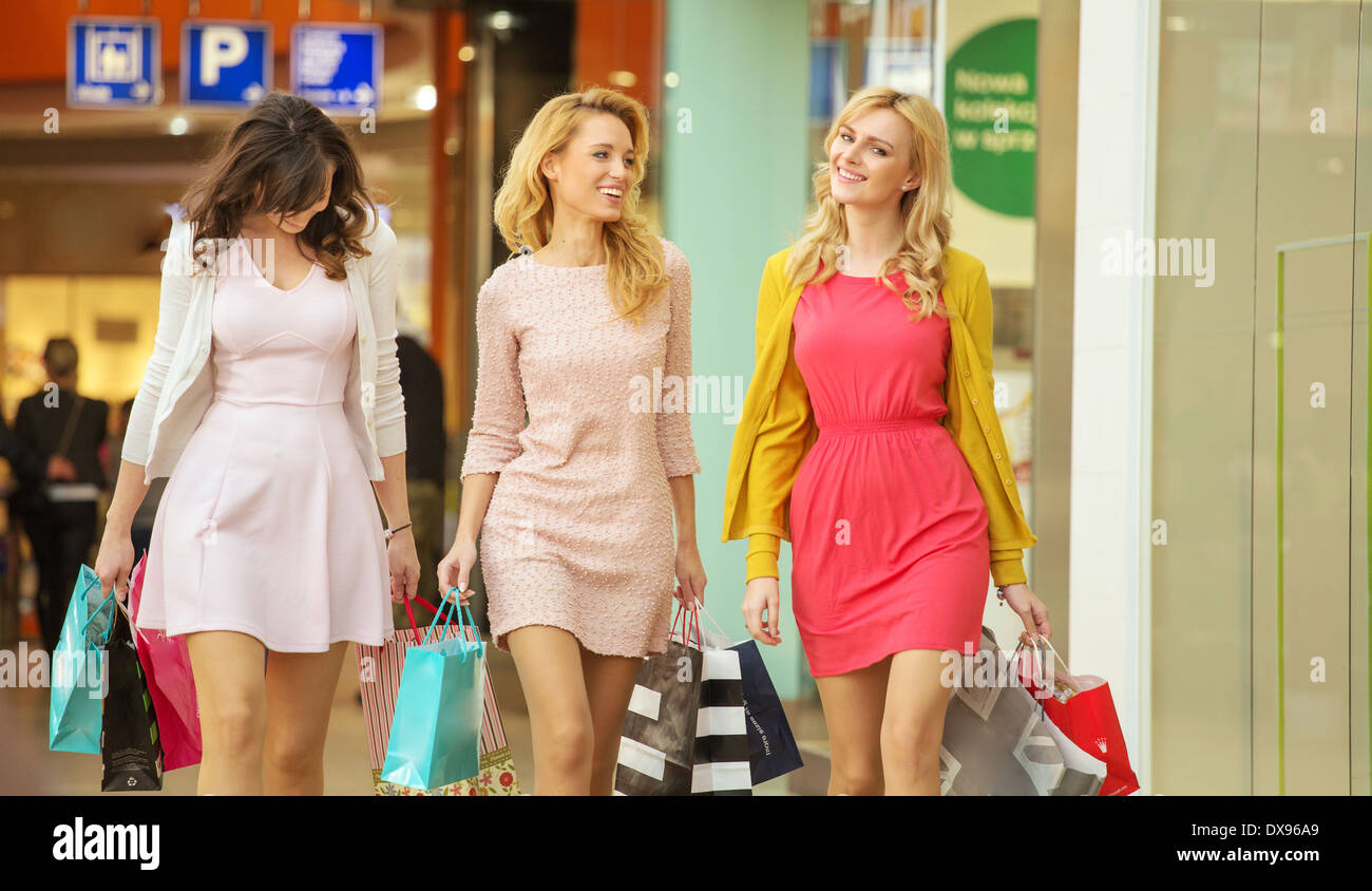 Three attractive women walking around the shopping mall - Stock Image
