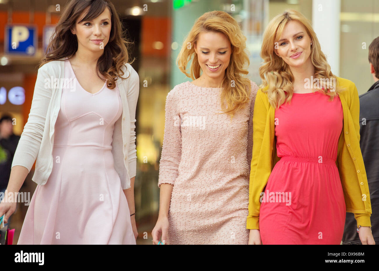 Three cheerful ladies in the shopping mall - Stock Image
