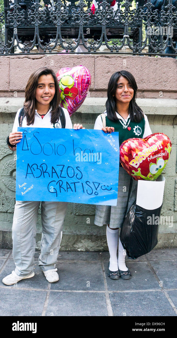 2 pretty high school girls with long dark hair advertise free hugs in front of Zocalo band shell on Valentines day 2014 Oaxaca - Stock Image