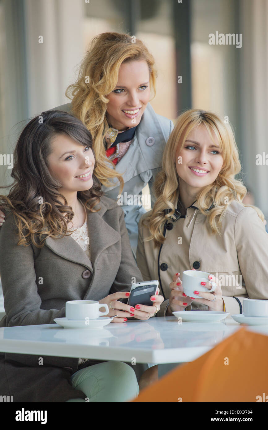 Three best friends in the cosy coffee shop - Stock Image