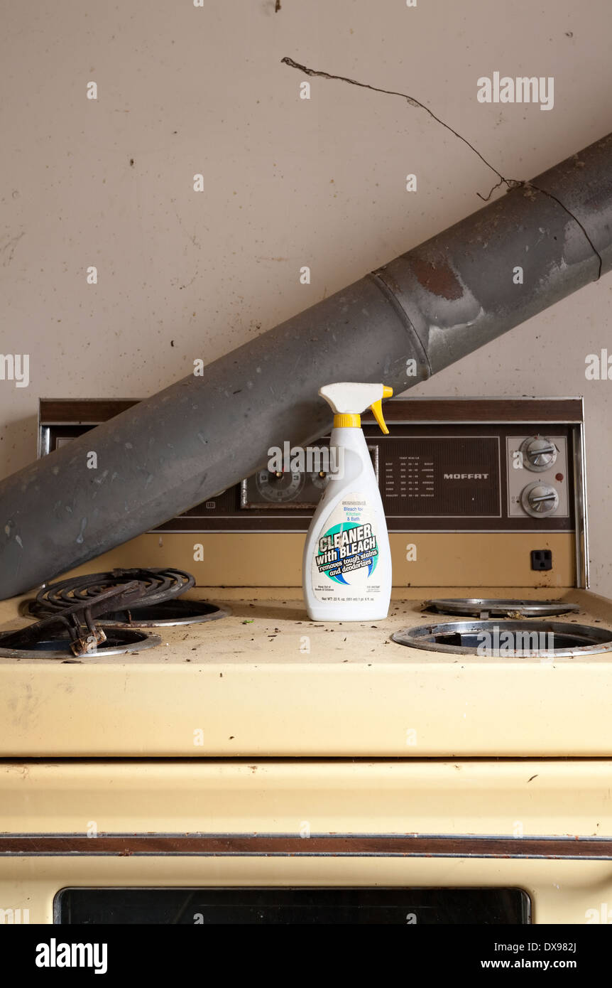 An old dirty and broken stove with a bottle of cleaner sitting on top in the Parry sound District of Northern Ontario, Canada. - Stock Image