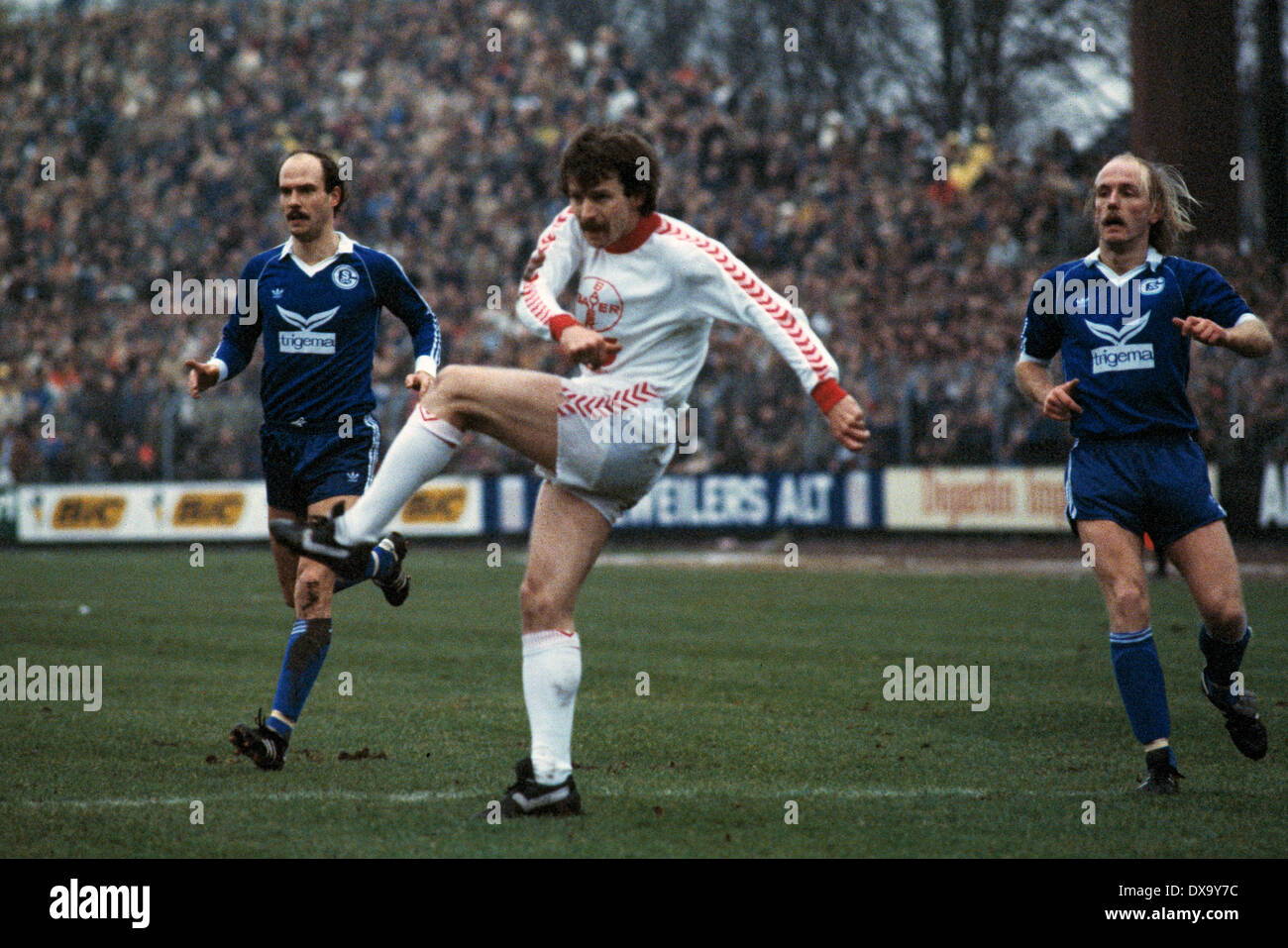 football, Bundesliga, 1980/1981, Grotenburg Stadium, FC Bayer 05 Uerdingen versus FC Schalke 04 1:3, scene of the match, shot on goal by Herbert Zimmer (Bayer), left Manfred Drexler (S04), right Ulrich Bittcher (S04) - Stock Image