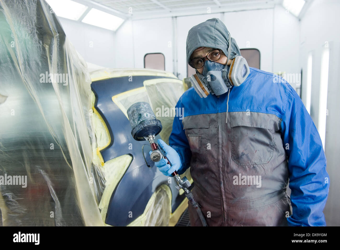 A professional car painter who is painting the body work of a car in a paint box of a garage with an airbrush. - Stock Image