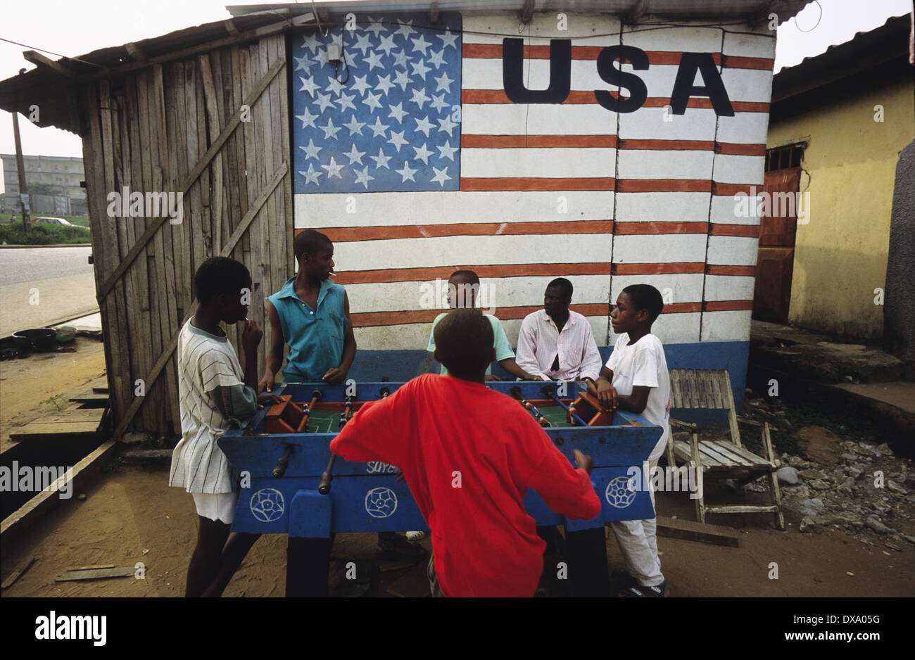 Children playing football under American flag mural, Yopougon township, across from Abidjan, Ivory Coast, Africa - Stock Image