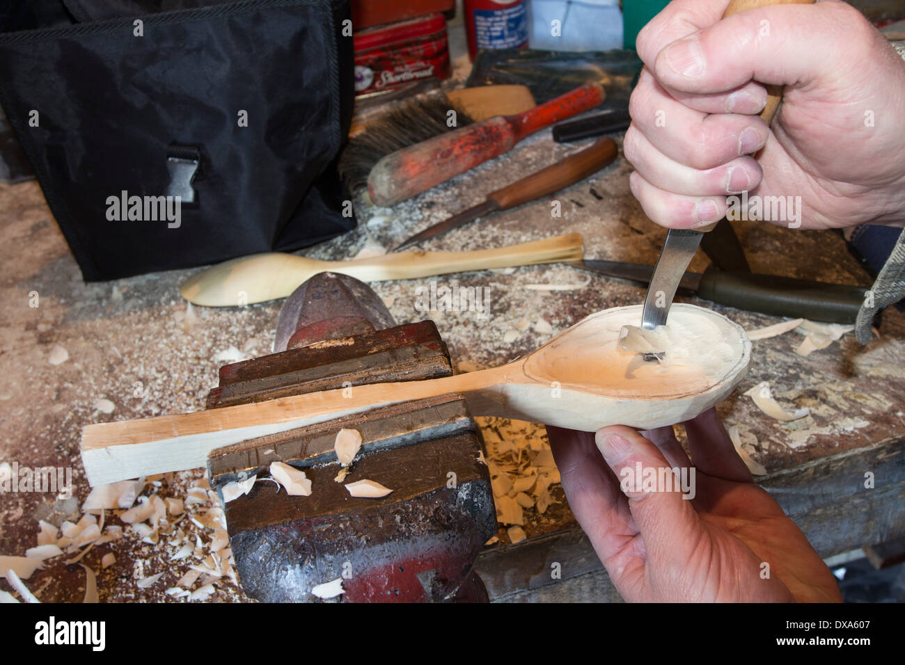 Spoon Carver Using a Crook Knife to Carve out the Bowl - Stock Image