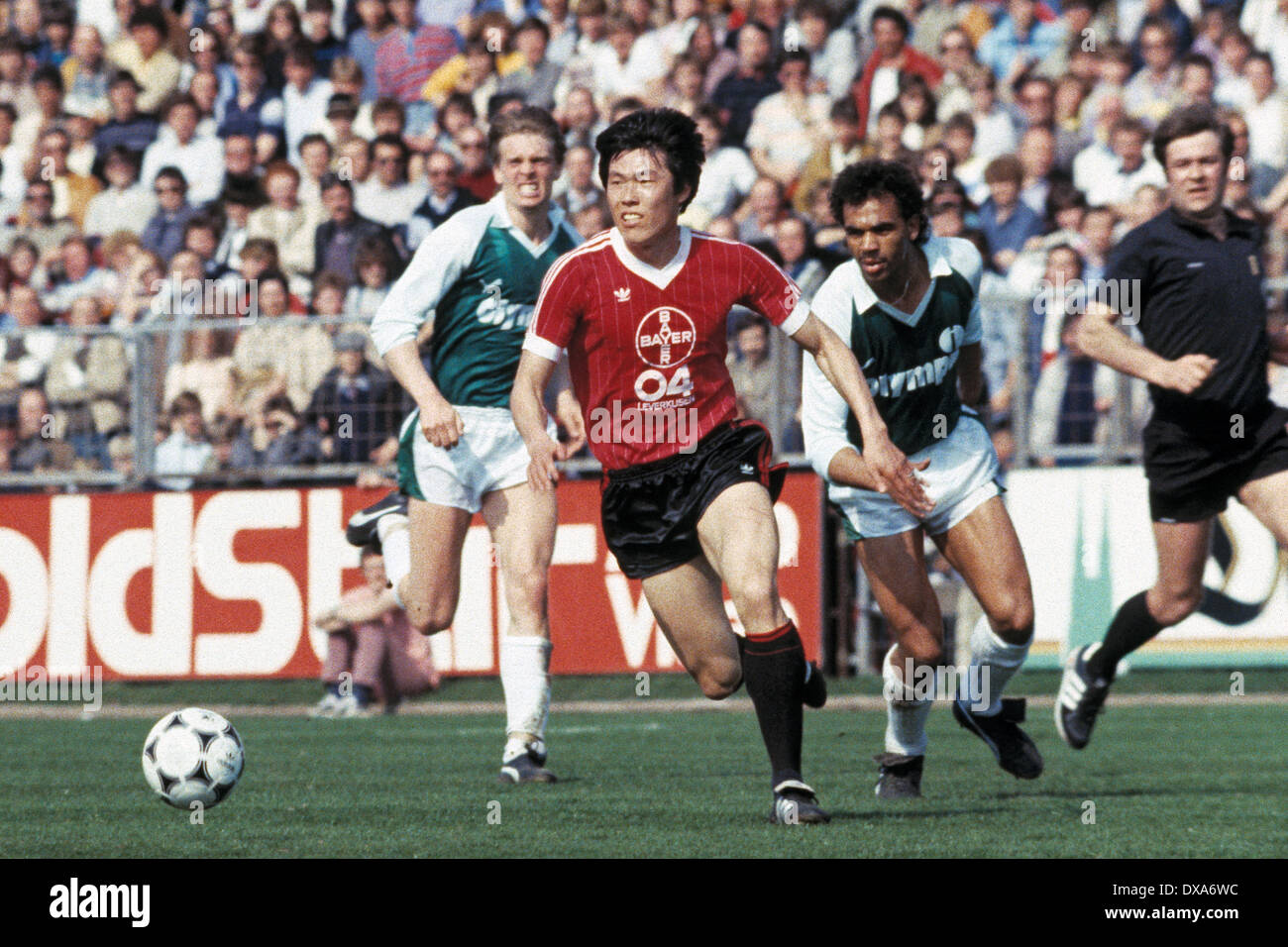 football, Bundesliga, 1983/1984, Ulrich Haberland Stadium, Bayer 04 Leverkusen versus SV Werder Bremen 0:0, scene of the match, f.l.t.r. Wolfgang Sidka (Werder), Bum-Kun Cha (Bayer) in ball possession, Rigobert Gruber (Werder), referee Heinz Werner - Stock Image