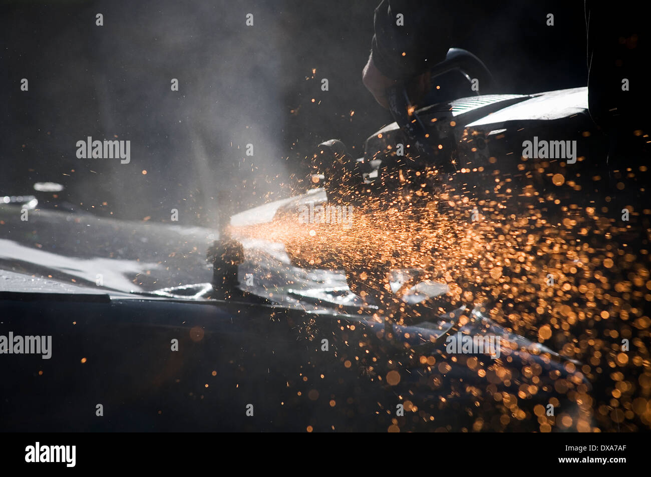 disk cutter cutting wheel angle grinder grinding cut steel metal sparks spark flying spray spraying of stihl saw saws grinders - Stock Image