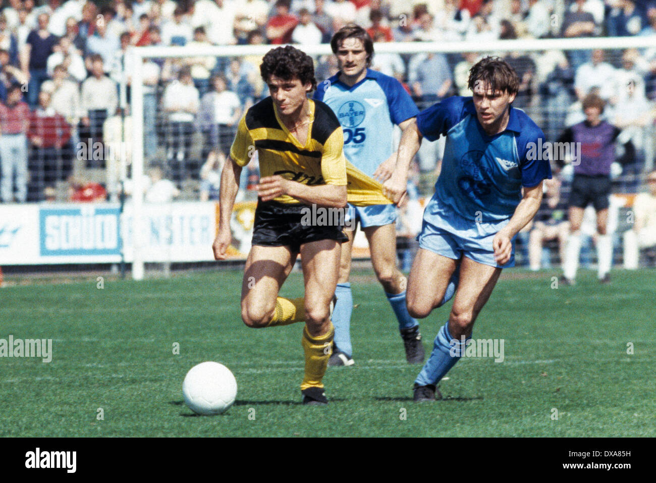 football, Bundesliga, 1983/1984, Grotenburg Stadium, FC Bayer 05 Uerdingen versus Borussia Dortmund 2:1, scene of the match, f.l.t.r. Erdal Keser (BVB) in ball possession, Horst Feilzer (Bayer), Wayne Thomas (Bayer) - Stock Image