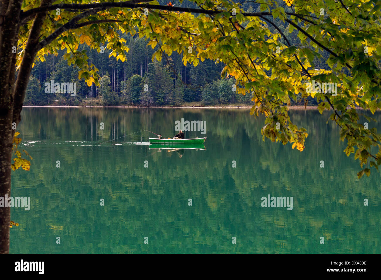 Angler fishing from rowing boat on the Walchensee / Lake Walchen in autumn, Upper Bavaria, Germany - Stock Image