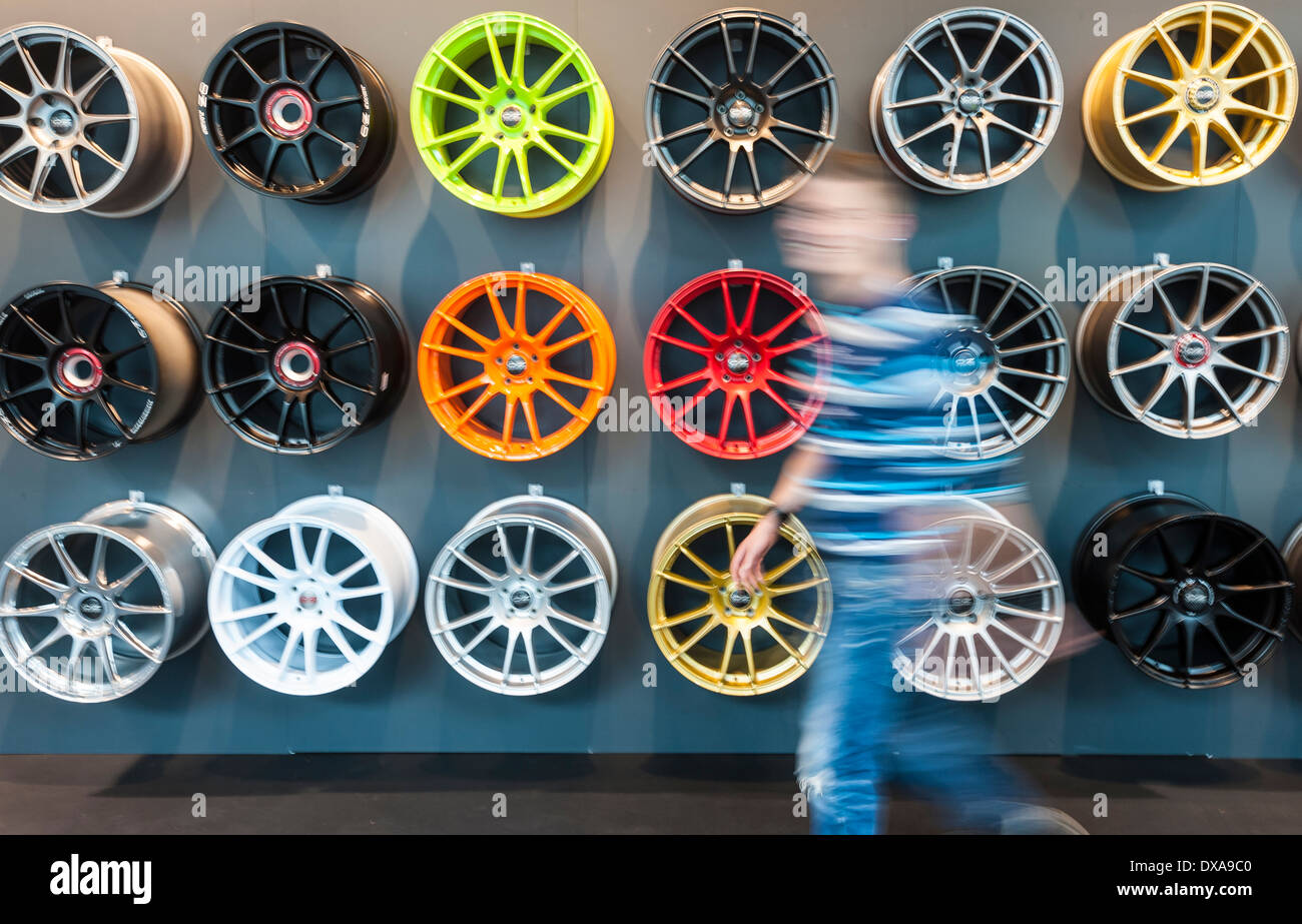 A visitors of the Zurich Motor Show passes by a wall of alloy rims at Switzerland's largest car exhibition - Stock Image