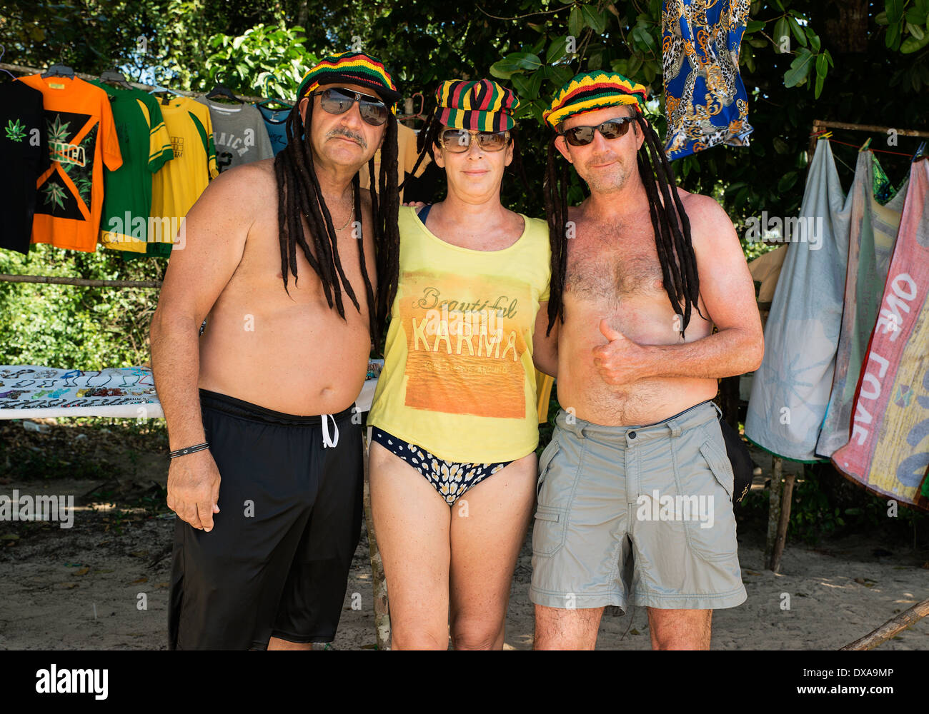 Tourist friends model dreadlock Jamaican hats on the beach, Negril, Jamaica - Stock Image