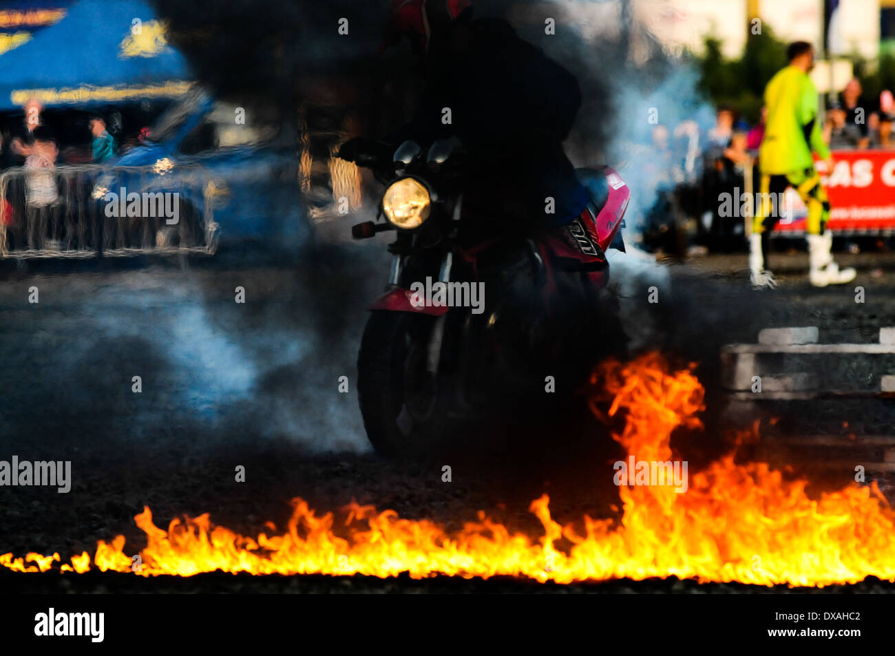 A dare devil performing a burnout on a motorbike while on fire. - Stock Image