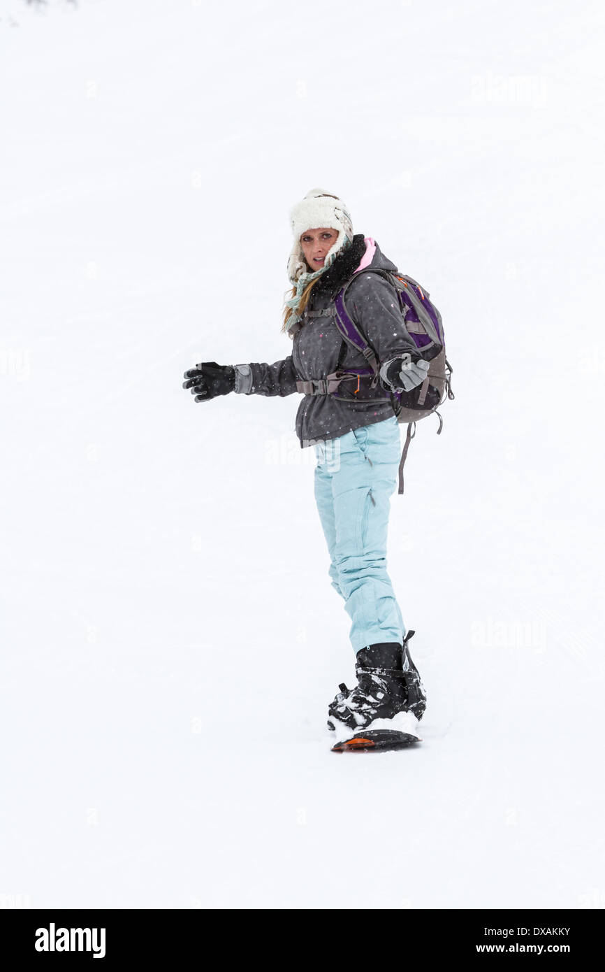 attractive woman snowboarding on the slopes of northern Idaho in snowy winter conditions - Stock Image