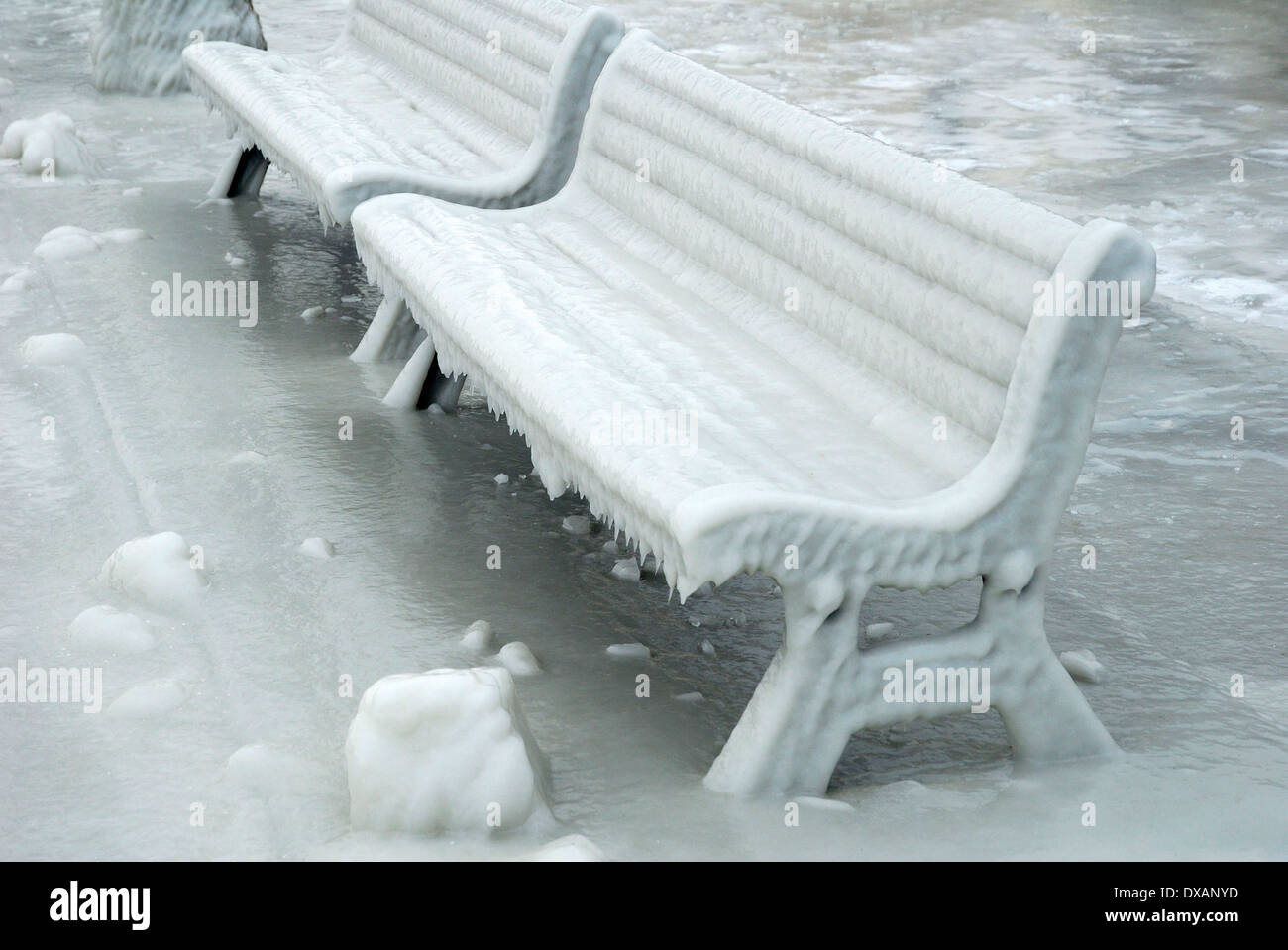 Benches covered with ice - Stock Image
