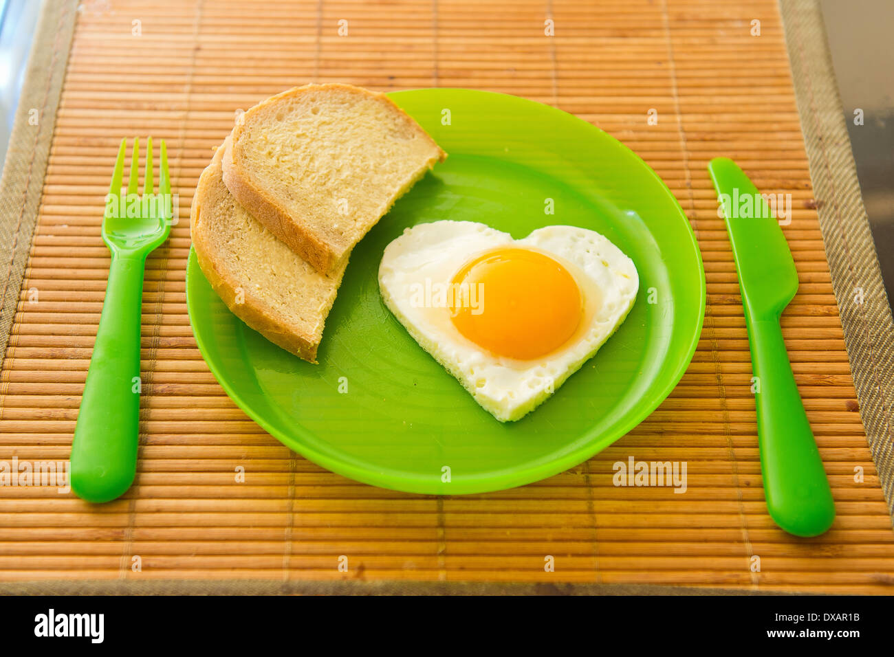 Fried egg in heart shape on green plastic plate - Stock Image