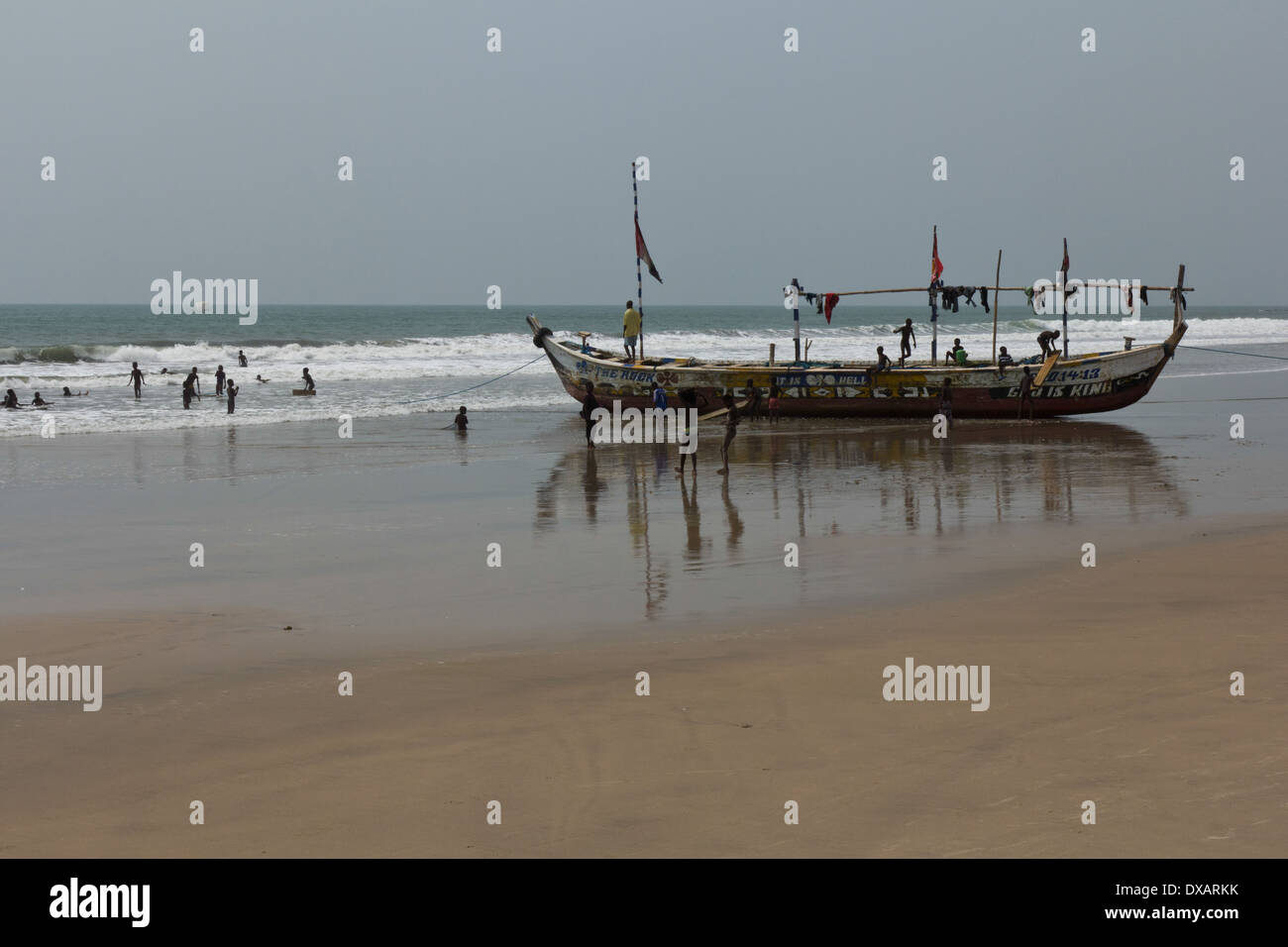 Children playing in fishing boat and in the sea at Kokrobite Beach, Ghana Stock Photo