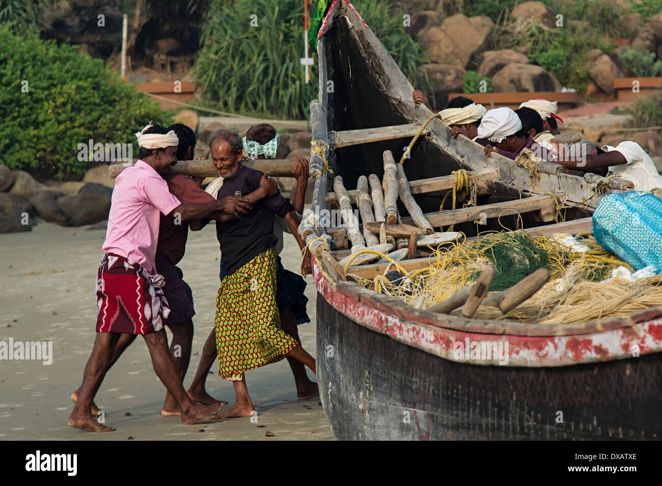 Fishermen moving their fishing boat into the sea at Lighthouse Beach in Kovalam, Kerala, India Stock Photo