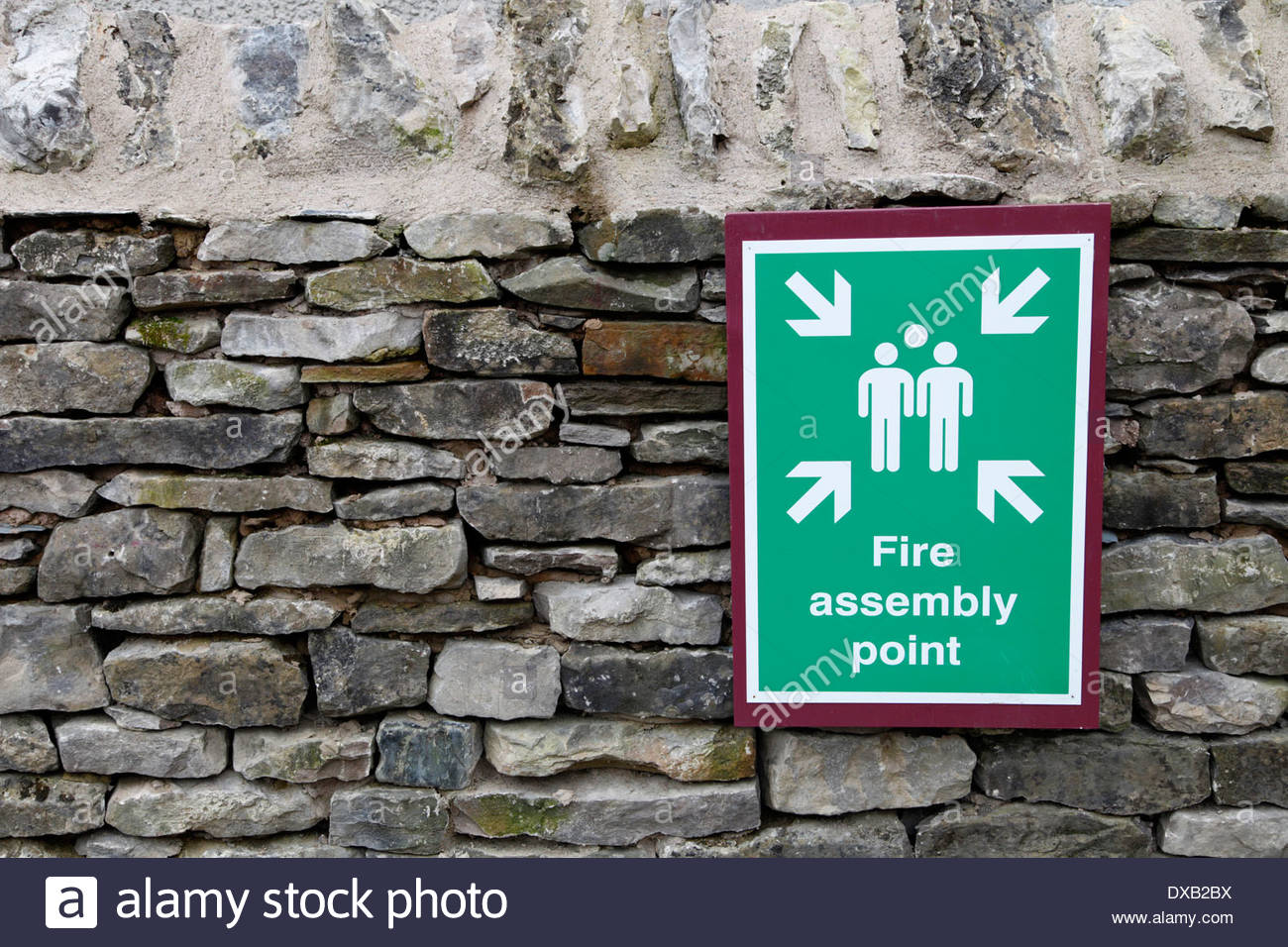 A green and white Fire Assembly Point sign, with stylized people and arrows, attached to a stone wall. - Stock Image