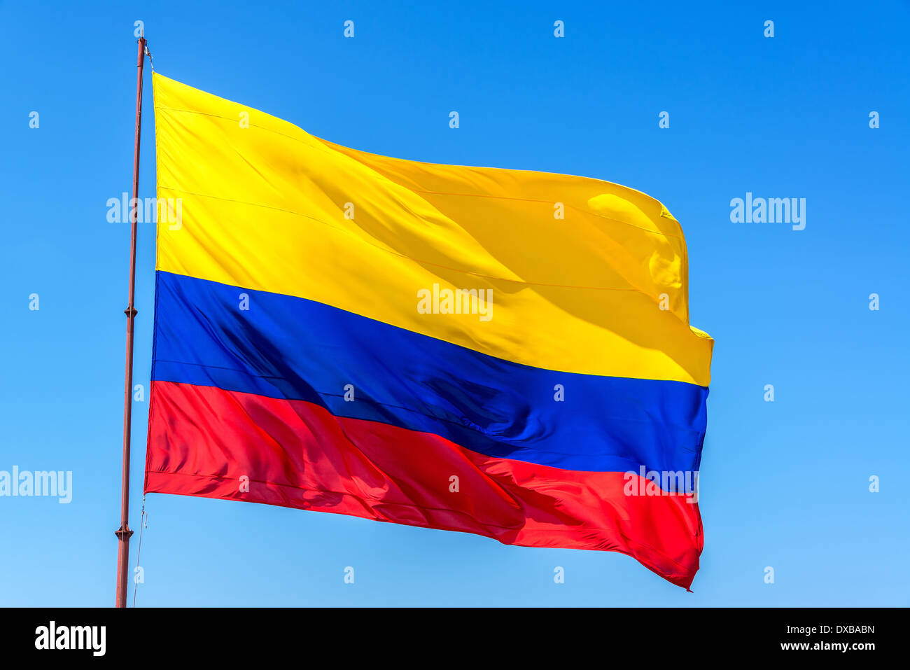 Resplendent Colombian flag waving in the wind set against a beautiful blue sky - Stock Image