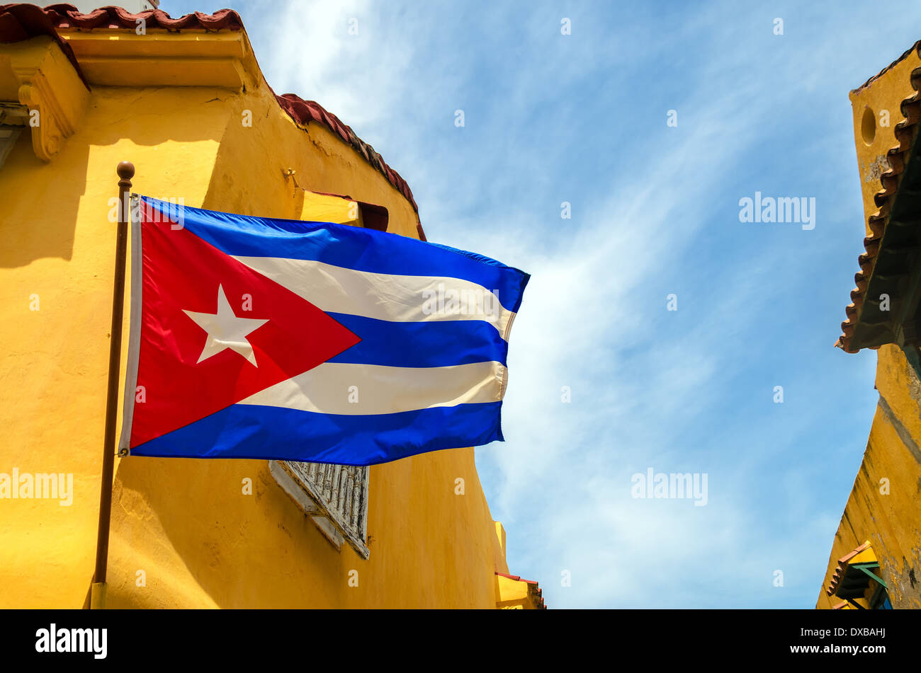 Cuban flag set against blue sky and yellow colonial buildings - Stock Image
