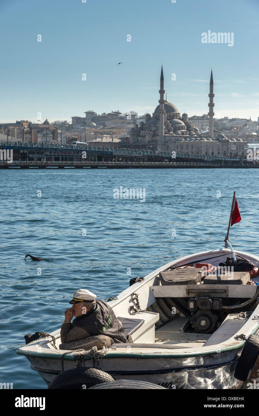 A boatman on Karakoy waterfront looks across the Golden Horn toward the Yeni mosque at Eminonu and the Istanbul skyline, Turkey. - Stock Image