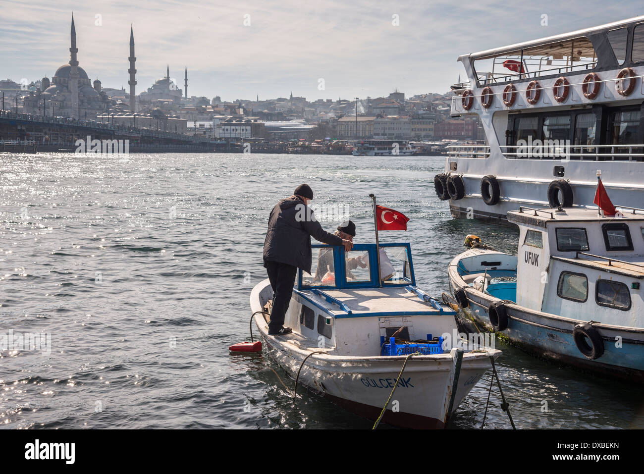 Boatmen on Karakoy waterfront looking across the Golden Horn toward the Yeni mosque at Eminonu and the Istanbul skyline, Turkey. - Stock Image
