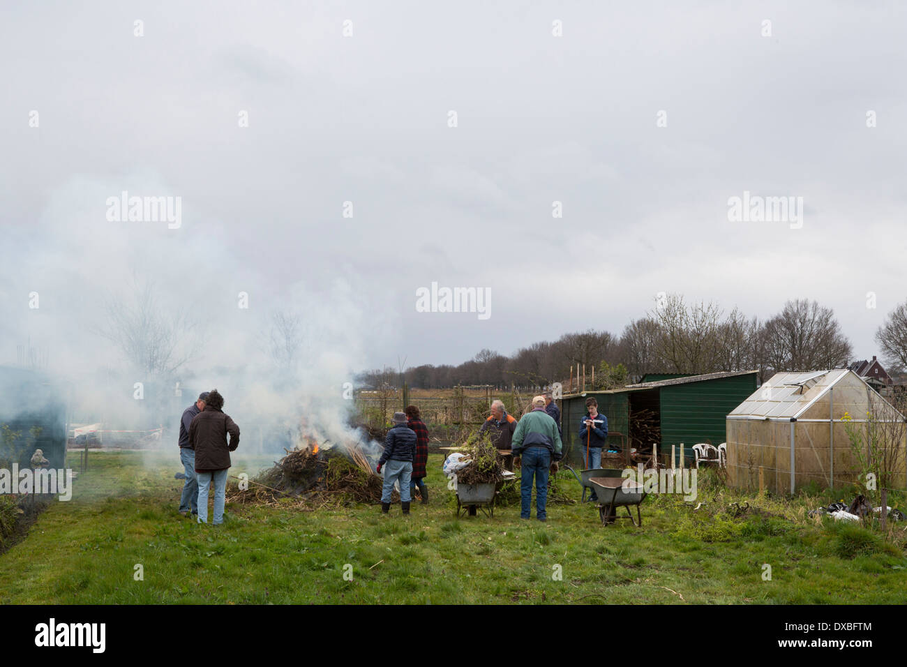 Cleaning day in the allotment garden. Group of gardeners standing around a fire where rubbish is being burned. Stock Photo