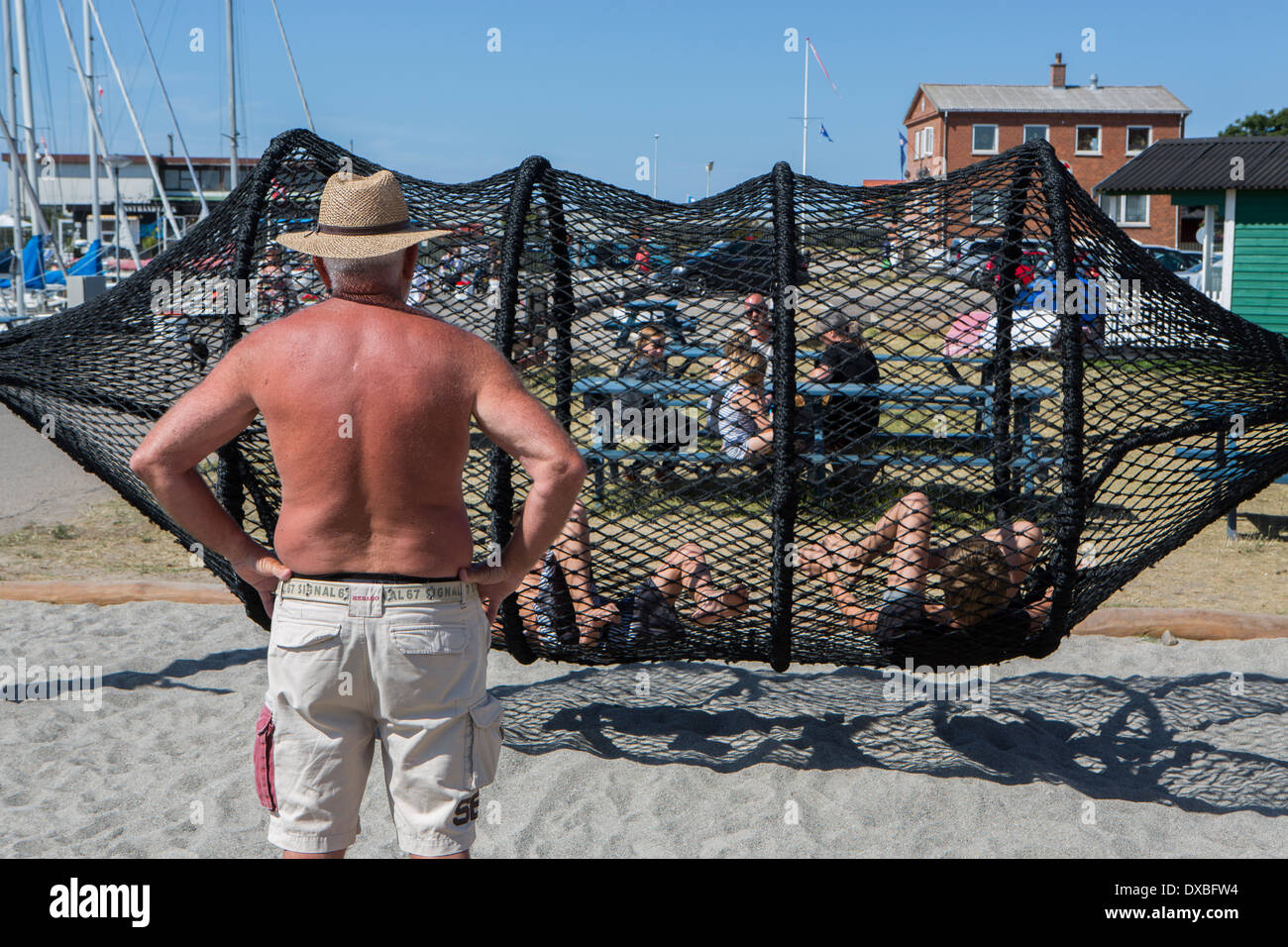 A man looks on as children play - Stock Image