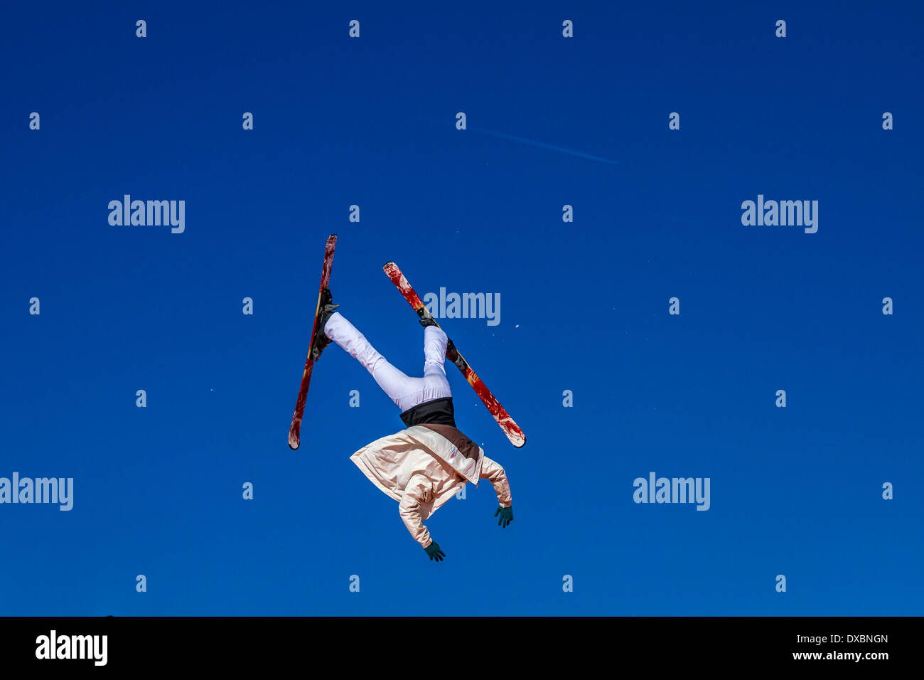 Skier upside down and out of control against a blue sky - Stock Image